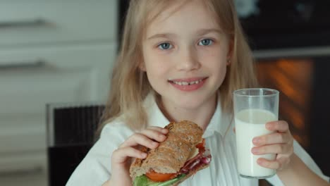 Closeup-Portrait-Of-A-Girl-The-Child-Holding-A-Sandwich-And-A-Glass-Of-Milk