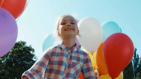 Closeup-Portrait-Of-Playful-Girl-Spinning-At-Camera-With-Balloons-In-The-Park