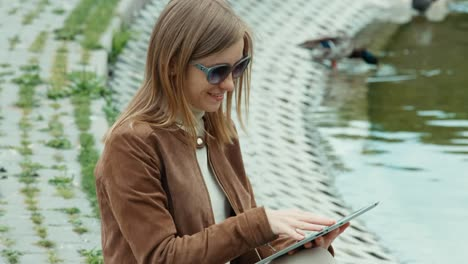 Closeup-Profile-Of-Young-Adult-Woman-Using-Tablet-PC-And-Sitting-On-The-Ground