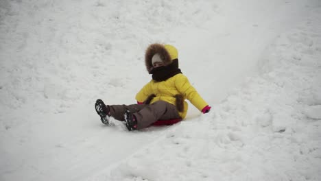 Cute-Little-Girl-Riding-Down-A-Steep-Hill-On-A-Sledge