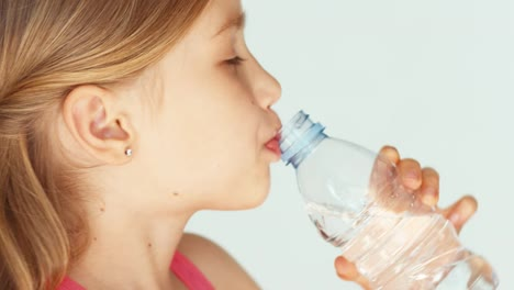 Extreme-Closeup-Portrait-Cute-Girl-Drinking-Water-From-Bottle-At-Camera