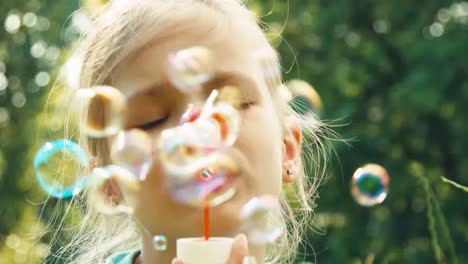 Extreme-Closeup-Portrait-Girl-Blowing-Soap-Bubbles-In-The-Grass-And-Smiling