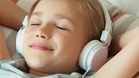 Extreme-Closeup-Portrait-Girl-Child-Listening-Music-In-Headphones-With-Eyes