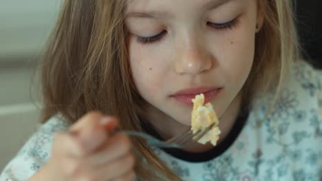 Extreme-Closeup-Portrait-Girl-Eating-Eggs-And-Looking-At-Camera