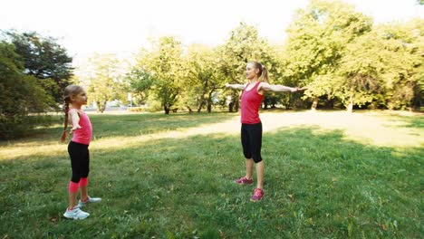 Family-Mother-And-Daughter-Performing-An-Exercise-In-The-Park-Camera-Flying