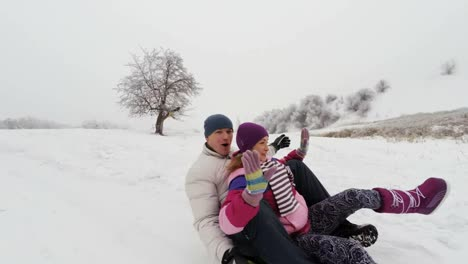 Family-Riding-Down-A-Steep-Hill-On-A-Toboggan