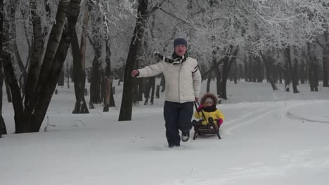 Father-Is-Pulling-The-Sledge-His-Daughter-In-A-Winter-Forest