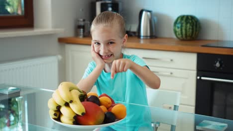 Girl-Advertises-Fruits-Child-Looking-At-Camera-And-Smiling