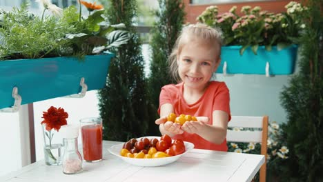 Girl-And-A-Handful-Of-Cherry-Tomatoes-Child-Giving-The-Viewer-Food-Smiling