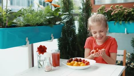 Niña-Y-Un-Puñado-De-Tomates-Cherry-Mirando-Y-Sonriendo-A-La-Cámara