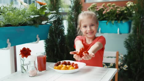 Girl-And-A-Handful-Of-Red-Cherry-Tomatoes-Looking-And-Smiling-At-Camera