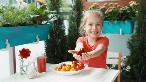 Girl-And-A-Handful-Of-Red-Cherry-Tomatoes-Looking-At-Camera
