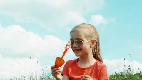 Girl-Blowing-Bubbles-Against-The-Sky-Child-Sitting-On-The-Grass-Against-Sky