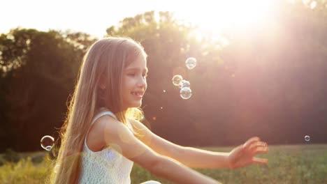 Mädchen-Fängt-Seifenblasen-Im-Sonnenlicht-Und-Lens-Flare-Glückliches-Kind-Lachend