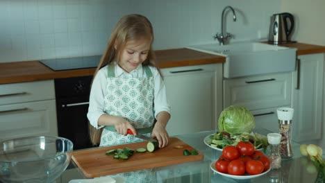 Mädchenkoch-In-Der-Küche-Der-Gurke-Schneidet-Und-In-Die-Kamera-Schaut-Und-Lächelt