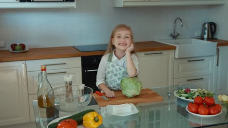 Girl-Chef-In-The-Kitchen-Looking-At-Camera-And-Smiling-Thumb-Up-Ok