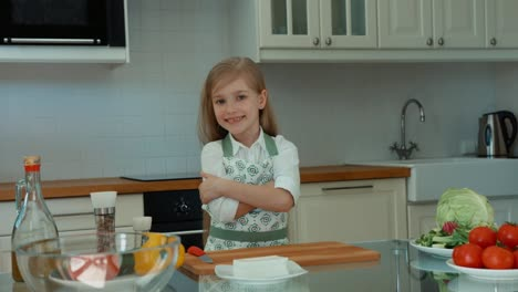 Girl-Chef-In-The-Kitchen-Looking-At-Camera-And-Smiling