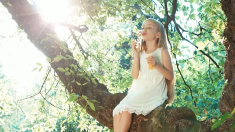 Girl-Child-68-Years-Playing-And-Blowing-Soap-Bubbles-On-A-Tree-Against-The-Sun