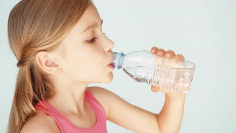Girl-Child-Drinking-Water-From-Bottle-At-Camera