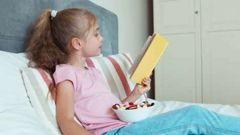 Girl-Child-Reading-A-Book-And-Eating-A-Sweets