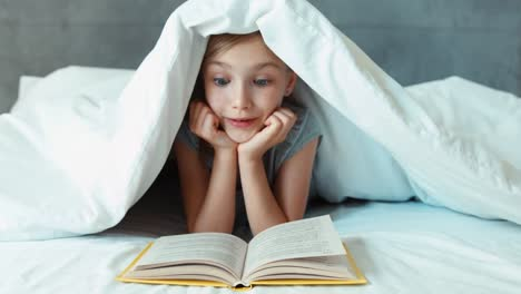 Girl-Child-Reading-Book-Under-The-Blanket-And-Smiling-At-Camera