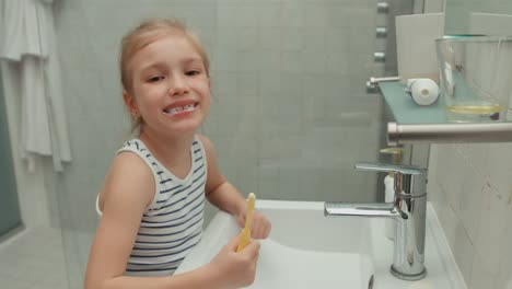 Girl-Cleaning-Teeth-After-Meals-And-Laughing-At-Camera