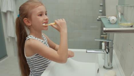 Niña-Limpiando-Los-Dientes-Después-De-Las-Comidas-Y-Mirando-A-La-Cámara