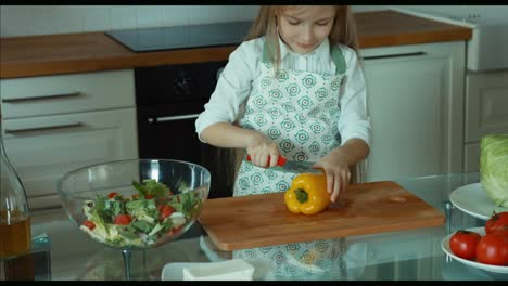 Girl-Cutting-Pepper-Child-Chef-In-The-Kitchen-Looking-At-Camera-And-Smiling