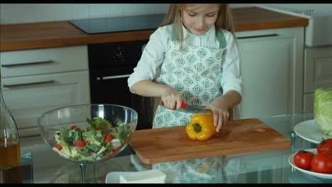 Mädchen-Schneidet-Pfeffer-Kinderkoch-In-Der-Küche-Mit-Blick-In-Die-Kamera-Und-Lächelt