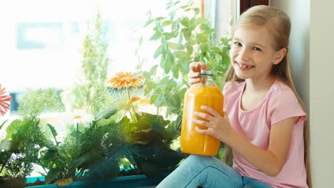 Girl-Drinking-Orange-Juice-From-Big-Bottle-And-Smiling-At-Camera