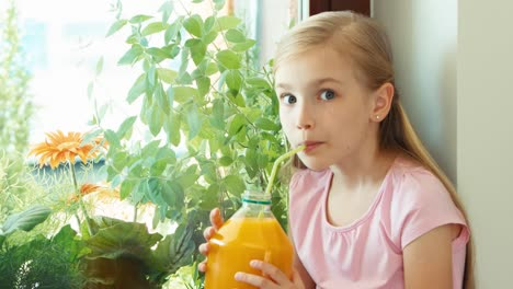 Girl-Drinking-Orange-Juice-From-Big-Bottle-Zooming