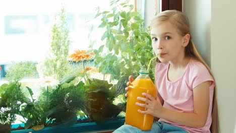 Girl-Drinking-Orange-Juice-From-Big-Bottle