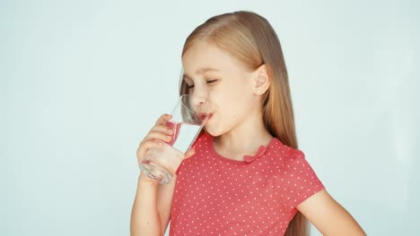 Girl-Drinking-Water-From-Glass-And-Smiling-At-Camera-Child-On-The-White