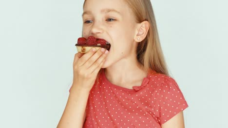 Girl-Eating-A-Cake-With-Raspberries-On-The-White-Background-Closeup
