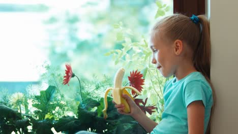 Girl-Eating-Banana-Child-Sitting-On-The-Windowsill-And-Looking-Out-The-Window-02