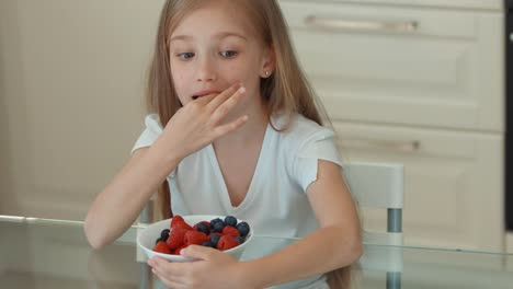 Girl-Eating-Blueberries-From-A-Plate-And-Smiling-At-Camera
