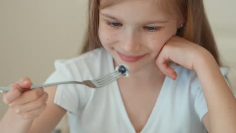 Girl-Eating-Blueberries-From-A-Plate-And-Smiling-At-The-Camera