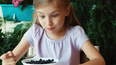 Girl-Eating-Blueberries-With-Sugar-And-Showing-Tongue-Child-Sitting-Resting