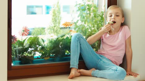 Girl-Eating-Cucumber-And-Sitting-On-The-Windowsill