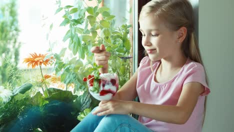 Girl-Eating-Ice-Cream-Against-Window-And-Smiling-At-Camera-The-Child-Nods