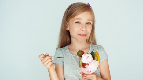 Girl-Eating-Ice-Cream-And-Smiling-At-The-Camera-On-The-White-Background
