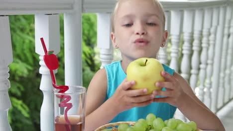 Niña-Comiendo-Manzana-Amarilla-En-La-Mesa-Sobre-La-Mesa-Es-Una-Cesta-De-Uvas