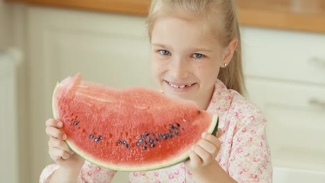 Girl-Holding-A-Big-Piece-Of-Watermelon-And-Smiling-At-Camera