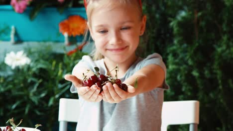 Girl-Holding-A-Handful-Cherry-And-Looking-At-Camera