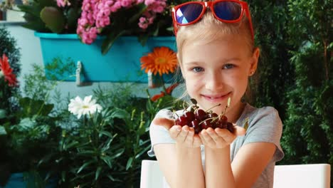 Girl-Holding-A-Handful-Cherry-Child-Admires-And-Looking-At-Camera-Zooming