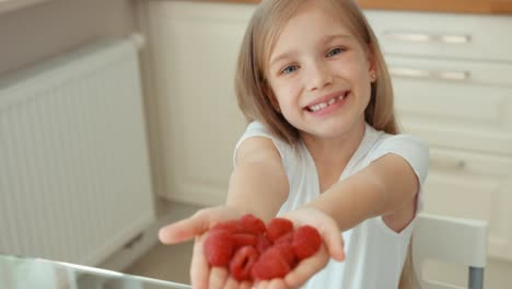 Girl-Holding-A-Handful-Of-Raspberries-And-Gives-Its-Audience-Looking-At-Camera