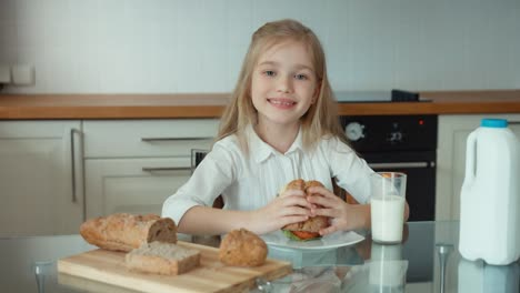 Girl-Holding-A-Sandwich-Smiling-At-Camera