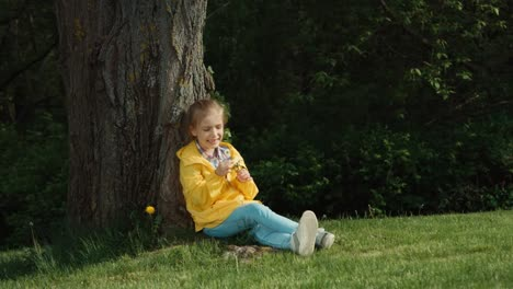 Girl-Holding-A-White-Flower-And-Looks-At-It-Girl-Sitting-Under-A-Tree