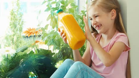 Girl-Holding-Bottle-Of-Orange-Juice-And-Smiling-At-Camera-Zooming