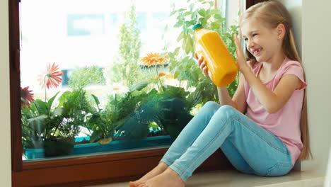 Girl-Holding-Bottle-Of-Orange-Juice-And-Smiling-At-Camera